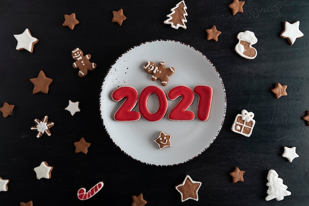 Bovenaanzicht smakelijke geglazuurde beschilderde koekjes: nummers 2021, sterren, dennenboom.