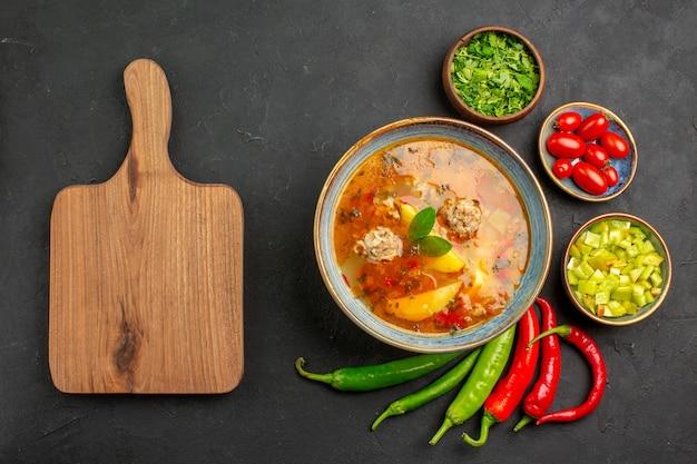 Bovenaanzicht smakelijke gehaktballen soep met greens en peper op de kleur van de schotel van de donkere tafelsaus