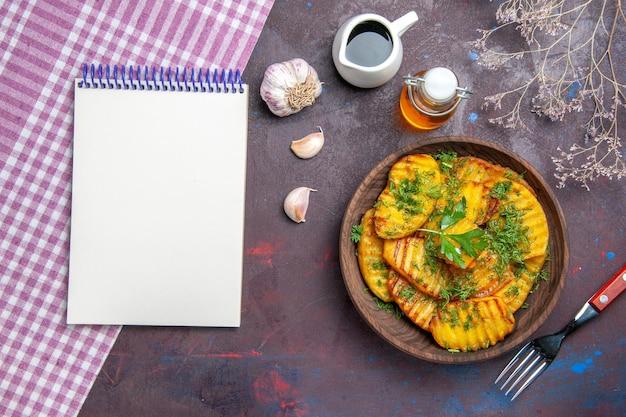 Bovenaanzicht smakelijke gekookte aardappelen heerlijke schotel met greens en notitieblok op het donkere oppervlak diner koken maaltijd aardappelschotel