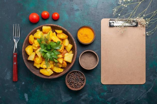 Bovenaanzicht smakelijke gekookte aardappelen met kruiden en blocnote op donkerblauwe achtergrond