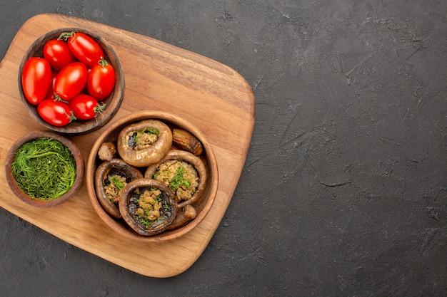 Bovenaanzicht smakelijke gekookte champignons met rode tomaten op donkere achtergrond