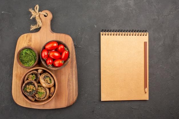 Bovenaanzicht smakelijke gekookte champignons met tomaten en greens op donker bureau
