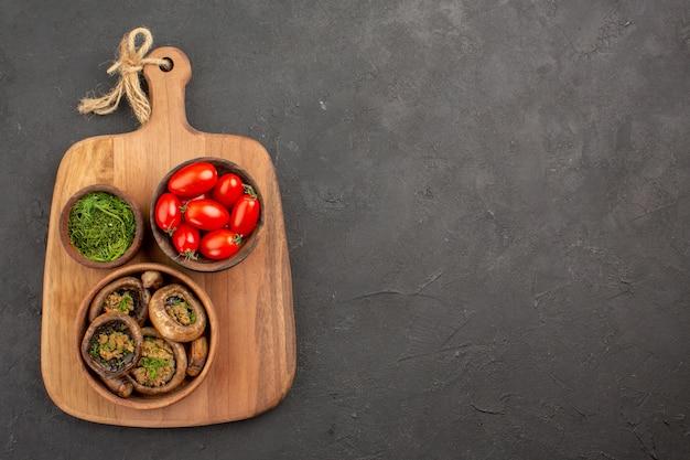Bovenaanzicht smakelijke gekookte champignons met tomaten en greens op donkere achtergrond