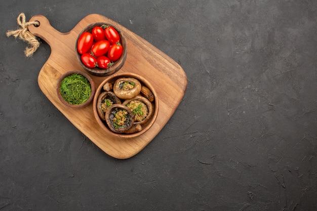 Bovenaanzicht smakelijke gekookte champignons met tomaten op donkere achtergrond