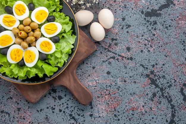 Bovenaanzicht smakelijke gekookte eieren met groene salade en olijven op lichte achtergrond