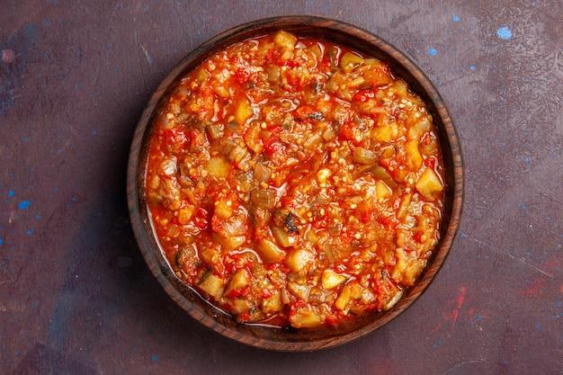Bovenaanzicht smakelijke gekookte groentesausmaaltijd met gesneden groenten op de donkere achtergrondmaaltijd van de de soepdiner van de voedselsaus