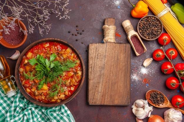 Bovenaanzicht smakelijke gekookte groentesausmaaltijd met verschillende kruiden en tomaten op donkere achtergrondsoep van de de maaltijdschotel van de voedselsaus