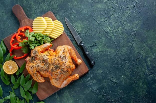 Bovenaanzicht smakelijke gekookte kip gekruid met aardappelen op de donkere achtergrond vleeskleur schotel maaltijd diner restaurant barbecue eten