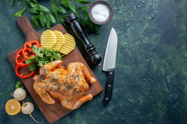Bovenaanzicht smakelijke gekookte kip gekruid met aardappelen op donkere achtergrond vleeskleur schotel barbecue diner eten restaurant