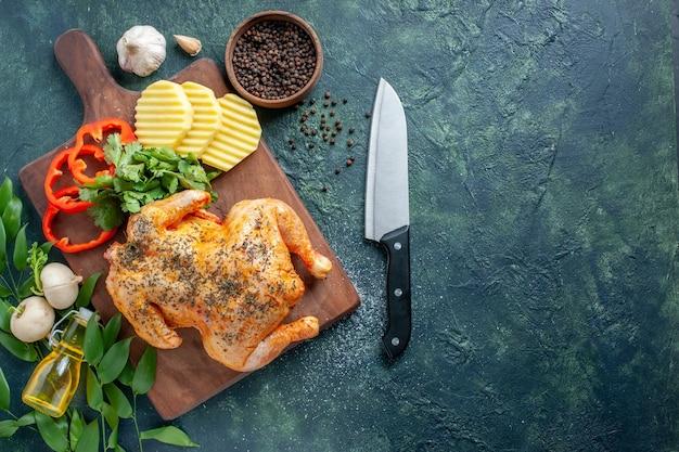 Bovenaanzicht smakelijke gekookte kip gekruid met aardappelen op donkere achtergrond vleeskleur schotel barbecue eten diner maaltijd