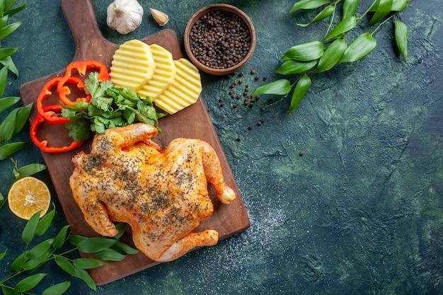 Bovenaanzicht smakelijke gekookte kip gekruid met aardappelen op donkere achtergrond vleeskleur schotel restaurant barbecue diner maaltijd