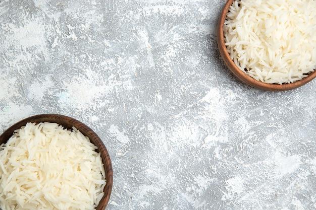 Bovenaanzicht smakelijke gekookte rijst in bruine borden op het wit