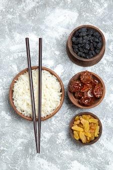 Bovenaanzicht smakelijke gekookte rijst in bruine plaat met rozijnen op licht wit