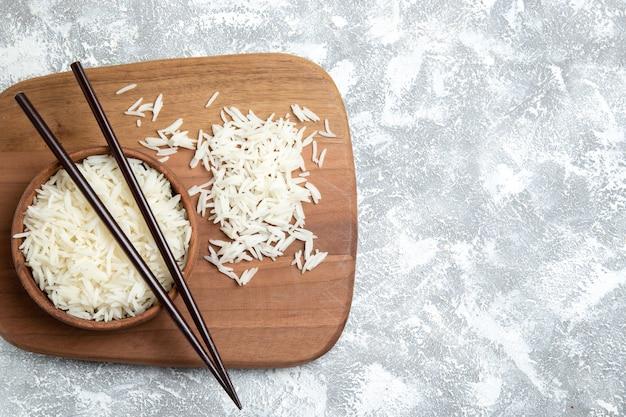 Bovenaanzicht smakelijke gekookte rijst in bruine plaat op licht wit