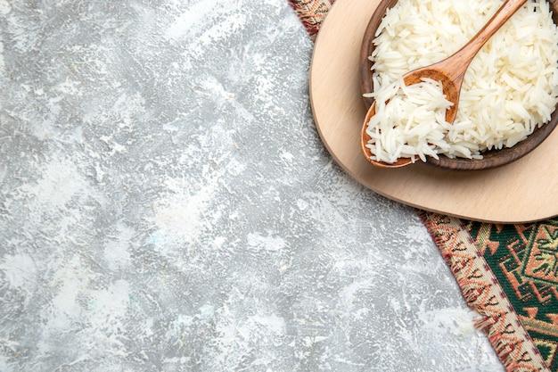 Bovenaanzicht smakelijke gekookte rijst in bruine plaat op wit
