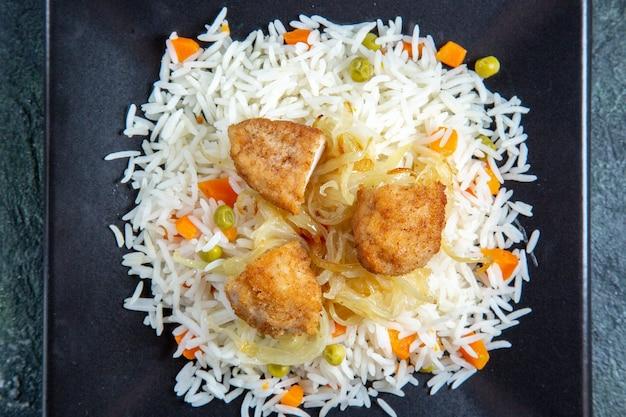 Bovenaanzicht smakelijke gekookte rijst met bonen en vlees in plaat op donker bureau