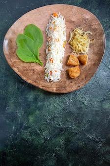 Bovenaanzicht smakelijke gekookte rijst met groene bladeren, bonen en vlees in plaat op donker bureau