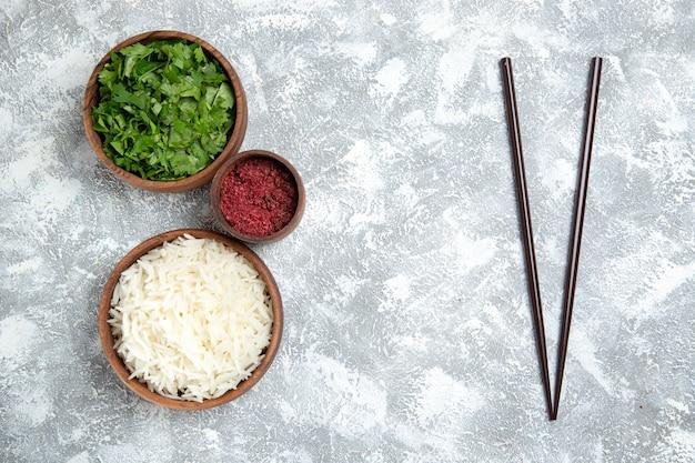 Bovenaanzicht smakelijke gekookte rijst met groenen op wit