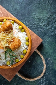 Bovenaanzicht smakelijke gekookte rijst met sperziebonen en vlees op donker bureau