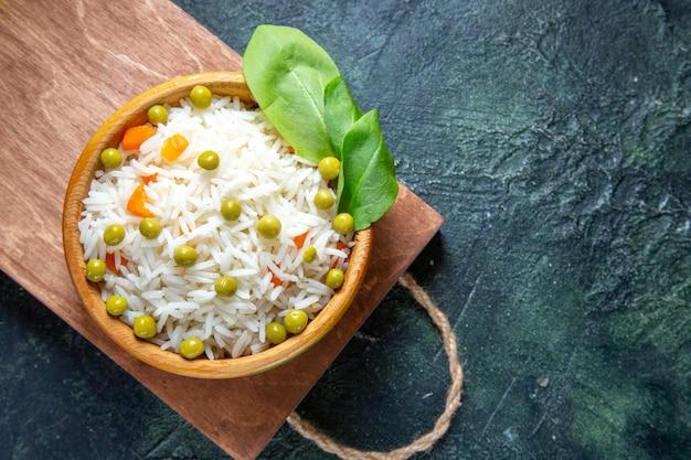Bovenaanzicht smakelijke gekookte rijst met sperziebonen in plaat op donker bureau