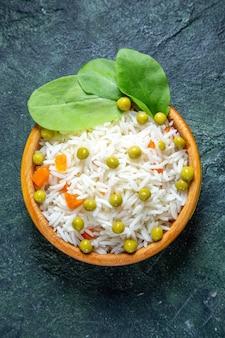 Bovenaanzicht smakelijke gekookte rijst met sperziebonen in plaatje op donker bureau