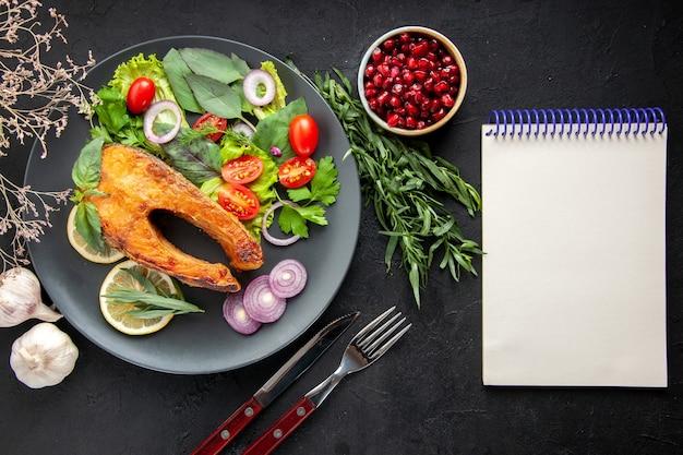 Bovenaanzicht smakelijke gekookte vis met verse groenten en kruiden op de donkere tafel