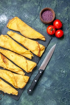 Bovenaanzicht smakelijke gerolde pannenkoeken bekleed met tomaten op de donkere achtergrondkleur maaltijd taart vlees deeg zoete hotcake gebak cake