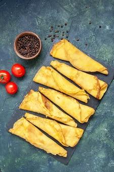Bovenaanzicht smakelijke gerolde pannenkoeken bekleed met tomaten op donkere achtergrond hotcake kleur maaltijd taart vlees deeg gebak taart zoet
