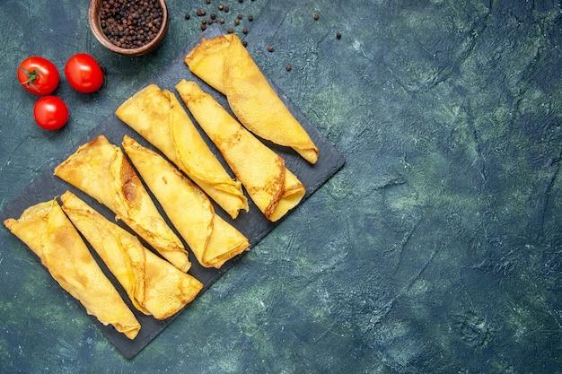 Bovenaanzicht smakelijke gerolde pannenkoeken bekleed met tomaten op donkere achtergrond hotcake kleur maaltijd taart vlees deeg zoete gebak cake