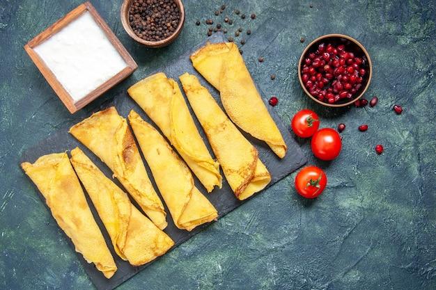 Bovenaanzicht smakelijke gerolde pannenkoeken bekleed met tomaten op donkere achtergrond hotcakes kleur maaltijd taart vlees deeg gebak taart zoet