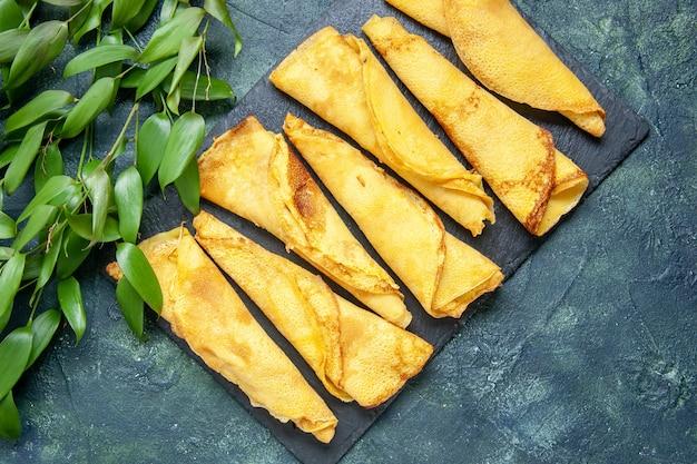 Bovenaanzicht smakelijke gerolde pannenkoeken bekleed op donkere achtergrondkleur maaltijd taart vlees deeg cake zoete hotcake gebak