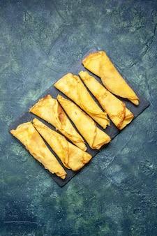 Bovenaanzicht smakelijke gerolde pannenkoeken bekleed op donkere achtergrondkleur maaltijd taart vlees deeg cake zoete hotcake