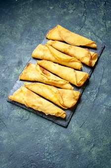 Bovenaanzicht smakelijke gerolde pannenkoeken bekleed op donkere achtergrondkleur maaltijd taart vlees gebak deeg zoete hotcake Gratis Foto