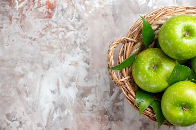 Bovenaanzicht smakelijke groene appels in mand op de lichte achtergrond