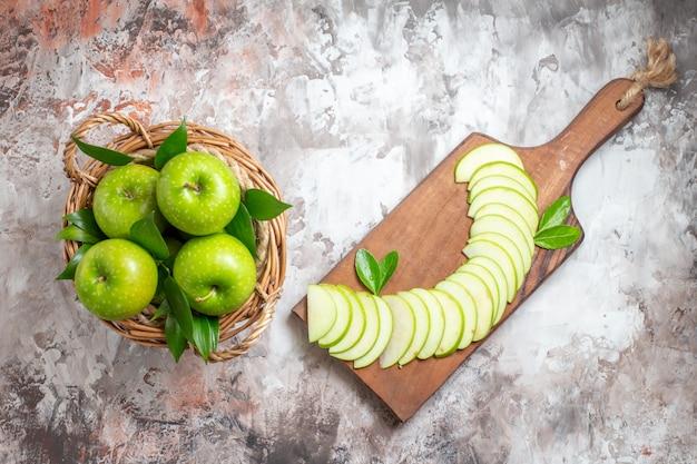 Bovenaanzicht smakelijke groene appels met gesneden fruit op de lichte achtergrond