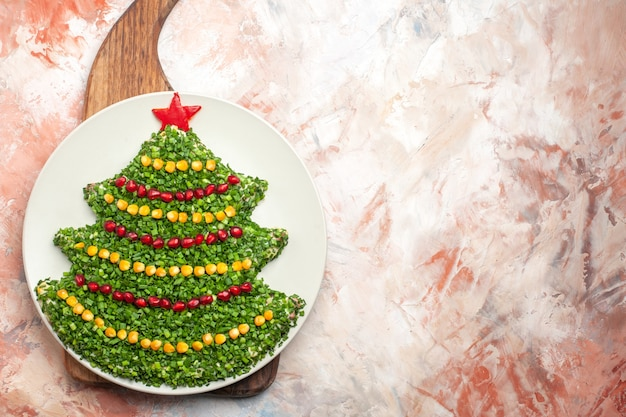 Bovenaanzicht smakelijke groene salade in de vorm van de nieuwe jaarboom binnen plaat op lichte achtergrond