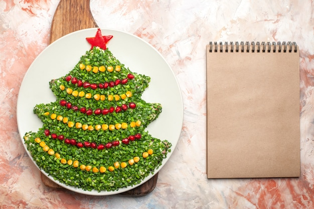 Bovenaanzicht smakelijke groene salade in de vorm van de nieuwe jaarboom in plaat met blocnote op lichte achtergrond