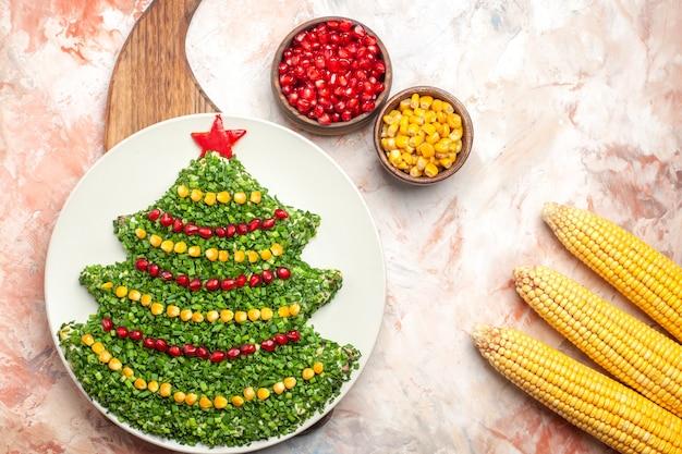 Bovenaanzicht smakelijke groene salade in de vorm van de nieuwe jaarboom met granaatappels en likdoorns op lichte achtergrond