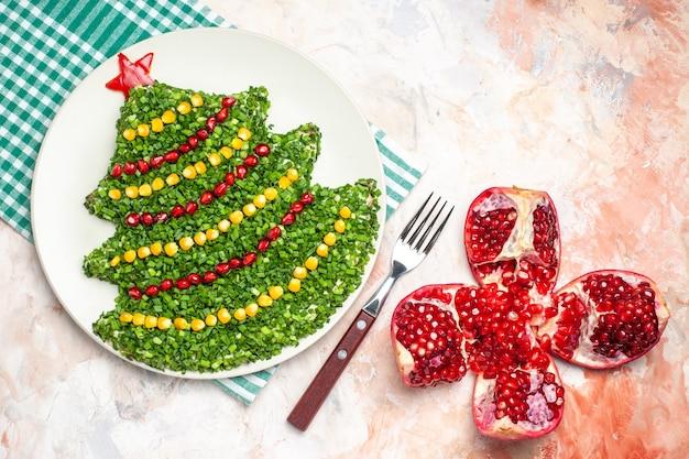 Bovenaanzicht smakelijke groene salade in de vorm van de nieuwe jaarboom met granaatappels op lichte achtergrond