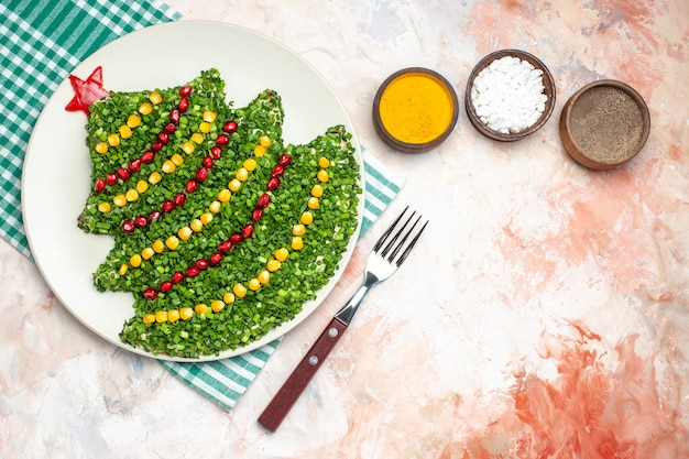 Bovenaanzicht smakelijke groene salade in de vorm van de nieuwe jaarboom met kruiden op lichte achtergrond