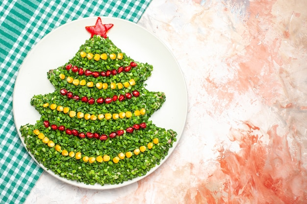 Bovenaanzicht smakelijke groene salade in kerstboomvorm op de lichte achtergrond