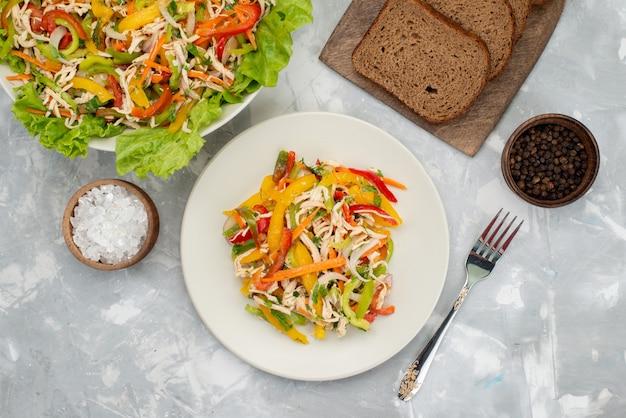 Bovenaanzicht smakelijke groente salade met gesneden groenten en groene salade met brood loafs op grijze, plantaardige salade maaltijd