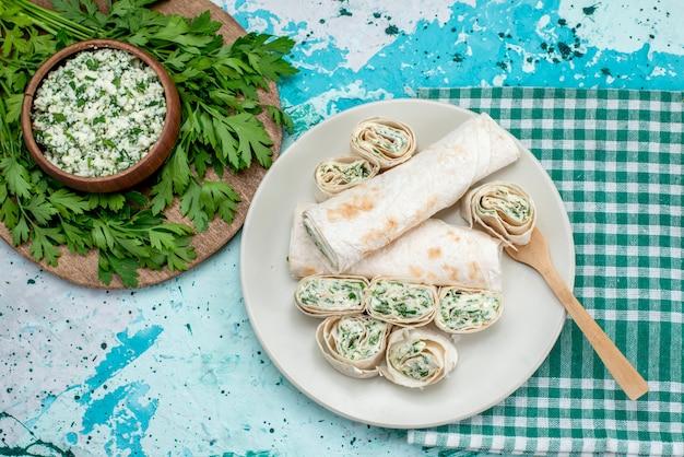 Bovenaanzicht smakelijke groentebroodjes geheel en in plakjes gesneden met greens en salade op de blauwe tafel