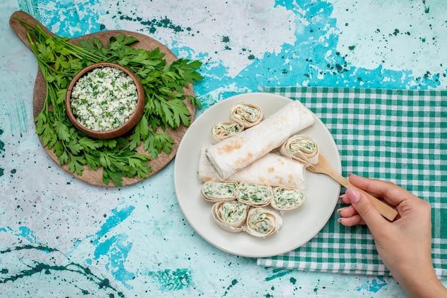 Bovenaanzicht smakelijke groentebroodjes geheel en in plakjes gesneden met greens en salade op het blauwe bureau