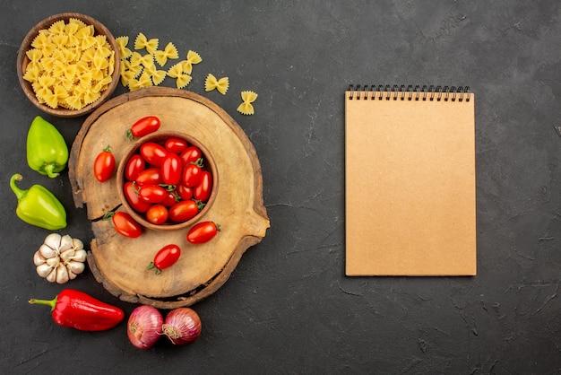 Bovenaanzicht smakelijke groenten snijplank met een kom tomatenpasta en paprika-ui-knoflook naast het crèmekleurige notitieboekje