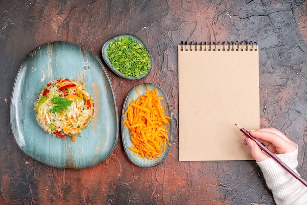 Bovenaanzicht smakelijke groentesalade binnen bord met greens en wortel op donkere tafel