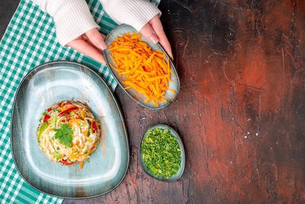 Bovenaanzicht smakelijke groentesalade in bord met vrouwelijke handen op de donkere tafel