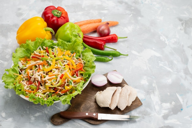 Bovenaanzicht smakelijke groentesalade met gesneden groenten en hele verse groenten en rauwe kipfilet op grijs, salade maaltijd