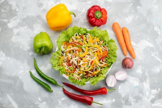 Bovenaanzicht smakelijke groentesalade met gesneden groenten en hele verse groenten op grijze, plantaardige salade maaltijd