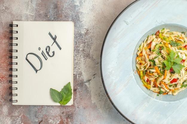 Bovenaanzicht smakelijke groentesalade met gesneden kip in plaat op lichte achtergrond
